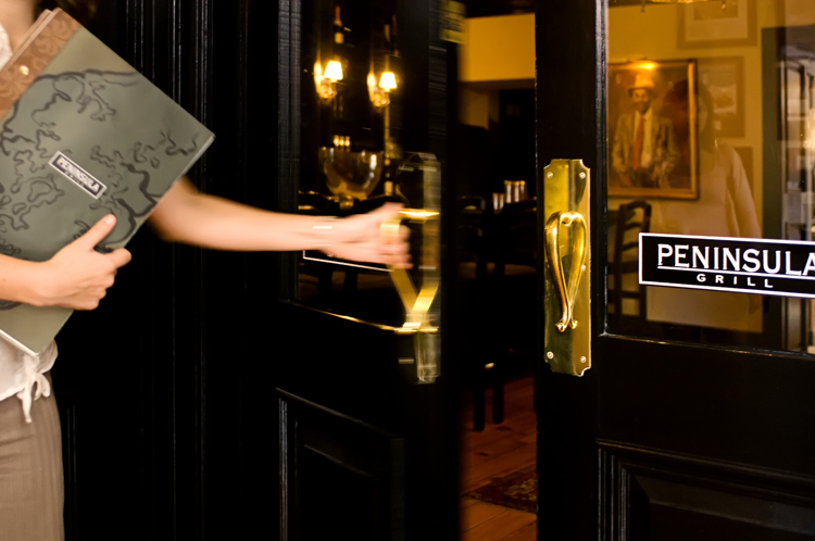 The gleaming black and gold doorway to Peninsula Grill, the iconic Charleston restaurant.