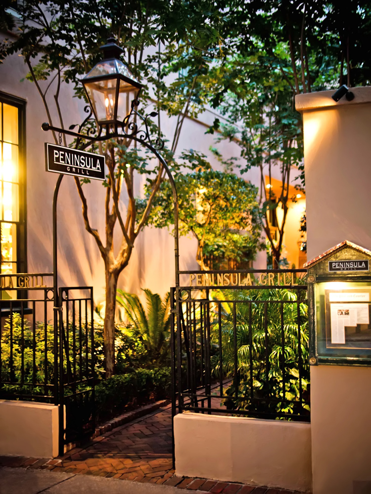The garden entry to Peninsula Grill in Charleston SC is lit by carriage lanterns.